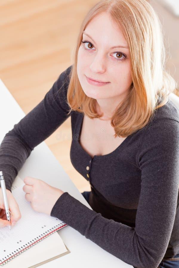 可爱的女性注意采取年轻人的学员 免版税库存照片