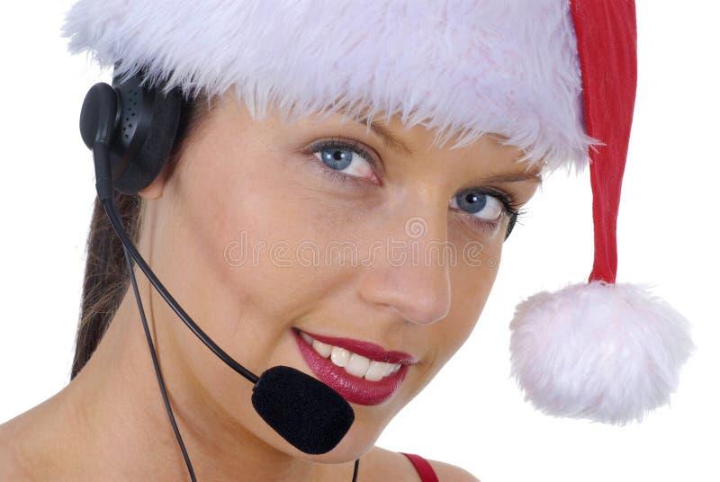 可爱的女性电话中心接线生佩带的圣诞节圣诞老人帽子特写镜头  免版税库存照片