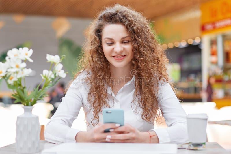 可爱的女性自由职业者在舒适咖啡馆检查重要notifcation,文本电子邮件,穿戴在白色女衬衫,有卷发,坐 库存照片