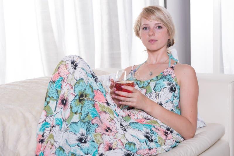年轻可爱的妇女享用在长沙发的一个鸡尾酒 库存照片