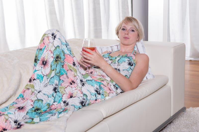 年轻可爱的妇女享用在长沙发的一个鸡尾酒 免版税库存图片
