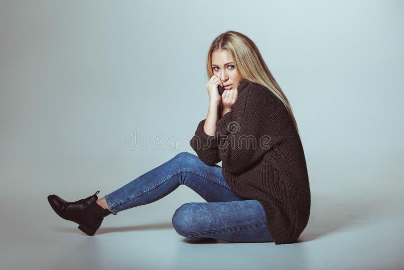 可爱的妇女佩带的毛线衣坐地板 图库摄影
