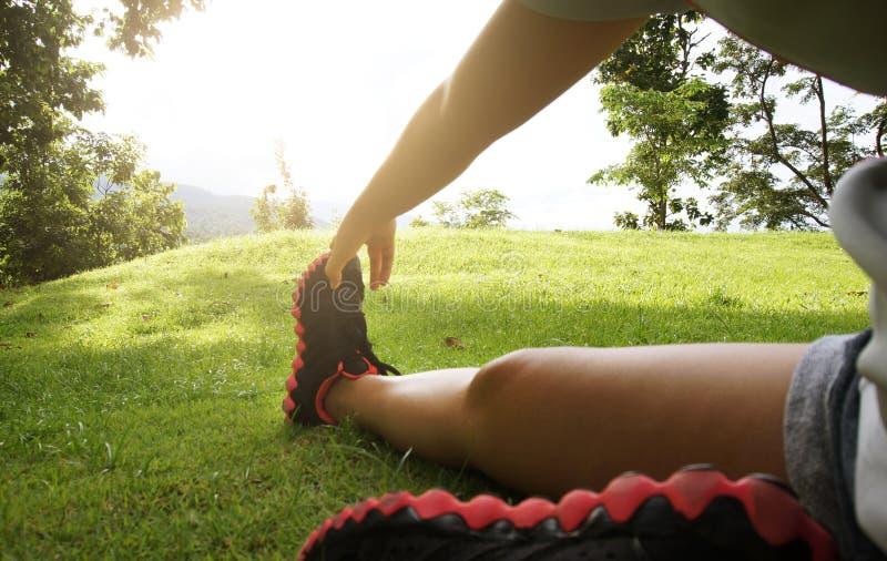 可爱的妇女使舒展锻炼兴奋他们的腿在w前 免版税库存照片