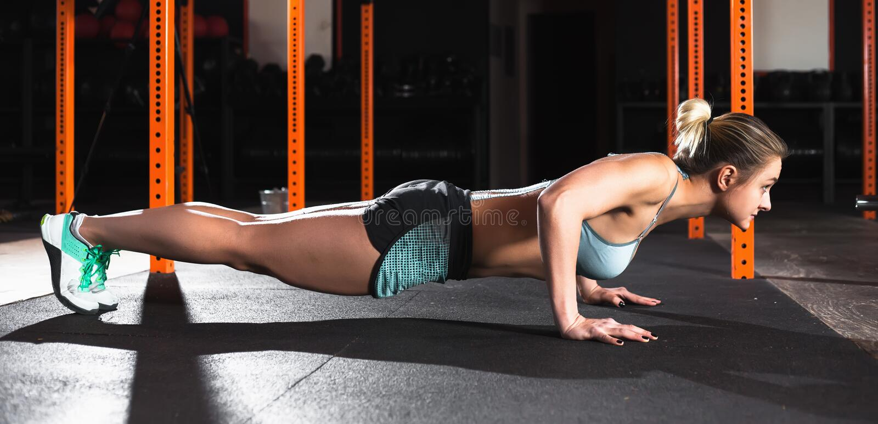 可爱的妇女做仰卧起坐锻炼 在健身房类的锻炼锻炼 免版税图库摄影