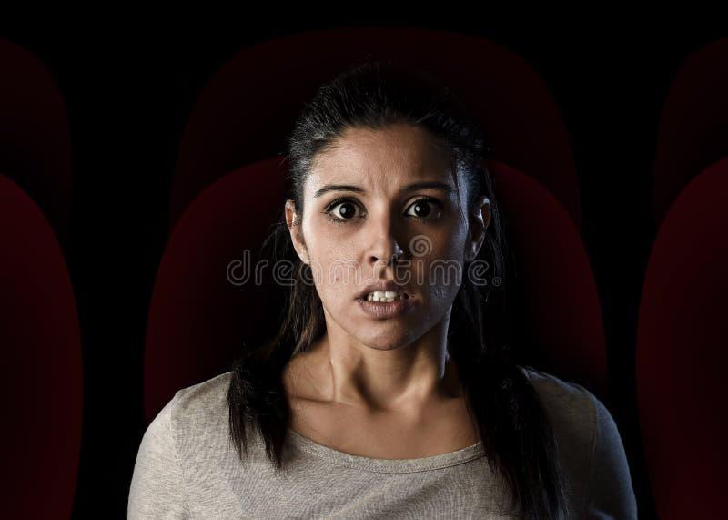 可爱的妇女单独观看的恐怖或担心戏曲电影在戏院大厅剧院 免版税库存图片