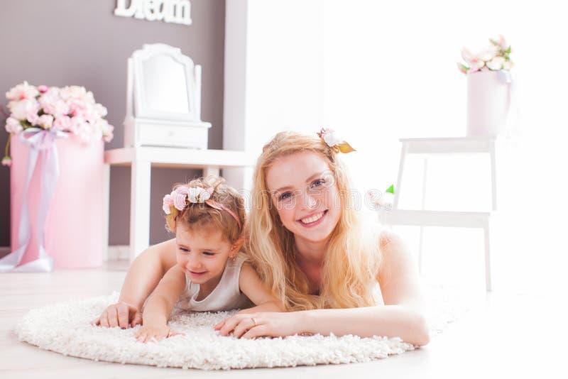 可爱的妇女和女孩一张软的地毯的在他们的房子里 库存照片