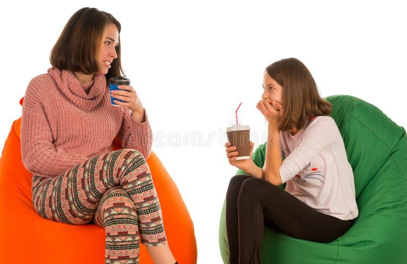 年轻可爱的妇女和女孩坐装豆子小布袋椅子, talki 免版税库存图片