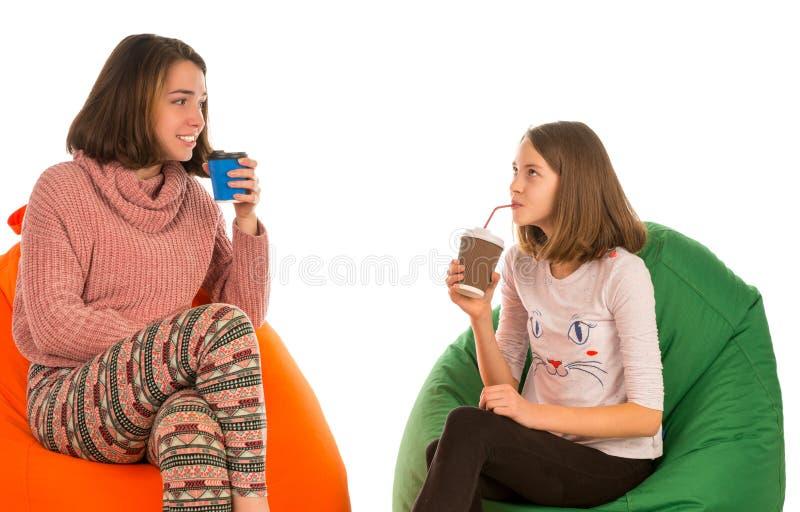 年轻可爱的妇女和女孩坐装豆子小布袋主席和博士 免版税库存图片