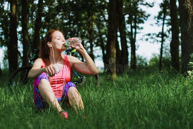 可爱的妇女喝从瓶的水 图库摄影