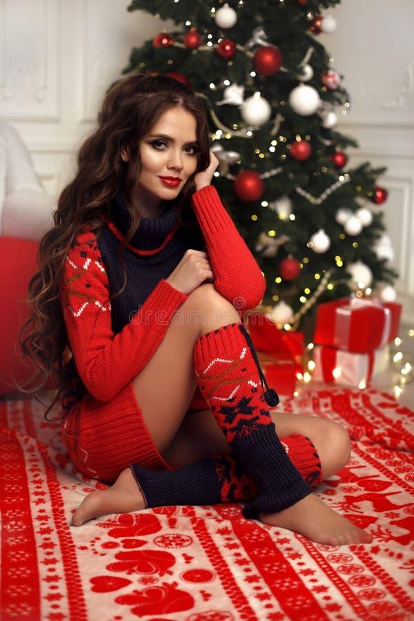 可爱的妇女圣诞节画象有卷曲发型的 有长发发型的美丽的深色的女孩在温暖的红色编织佩带 库存照片