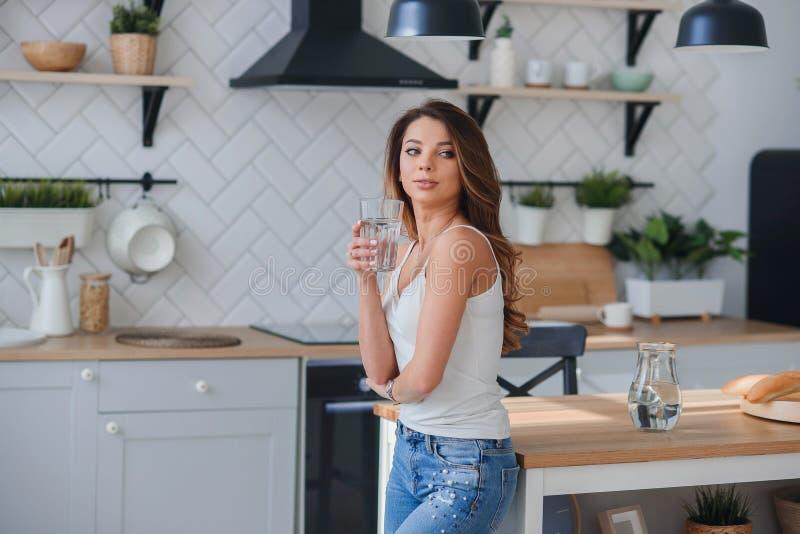 可爱的妇女在早晨喝纯净的水在厨房里 医疗保健和饮食概念 免版税库存图片