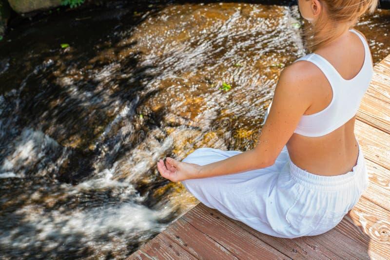 可爱的妇女在早晨实践瑜伽和凝思,坐在莲花姿势在瀑布附近 免版税库存照片