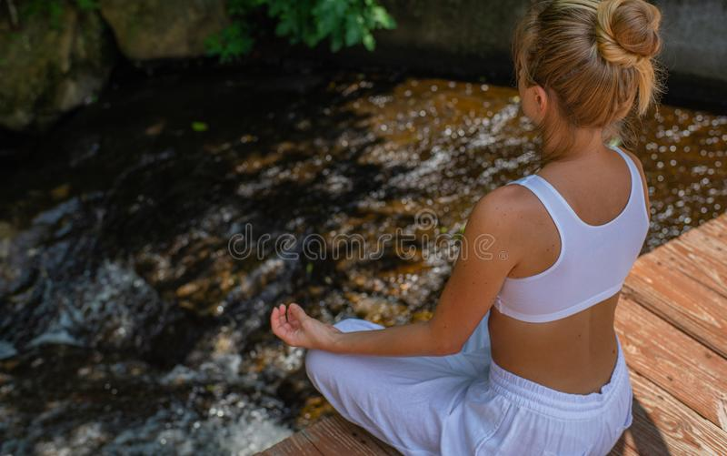 可爱的妇女在早晨实践瑜伽和凝思,坐在莲花姿势在瀑布附近 库存照片