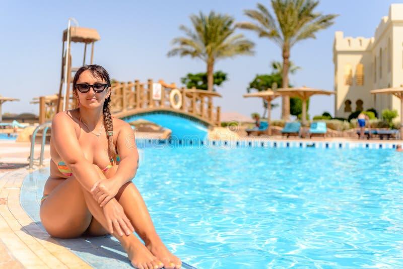 可爱的妇女在比基尼泳装游泳池边 免版税图库摄影