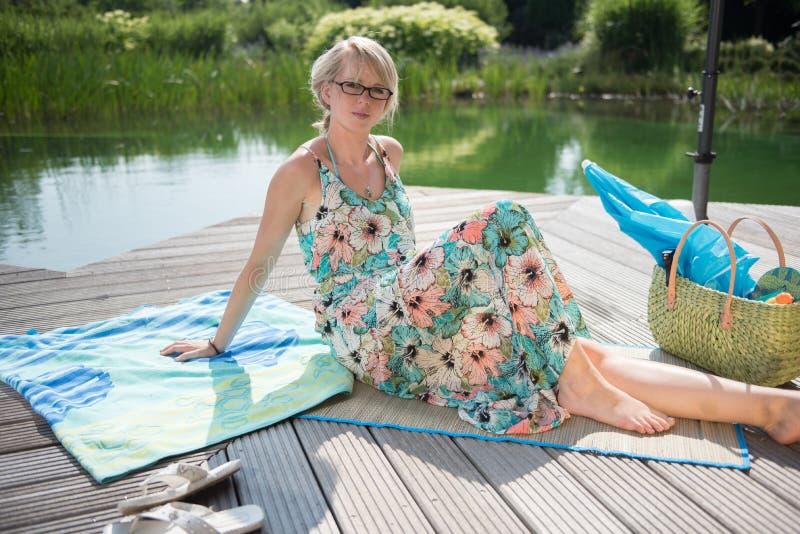 年轻可爱的妇女坐在水池 免版税库存照片