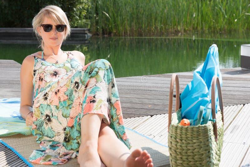 年轻可爱的妇女坐在水池 免版税库存图片