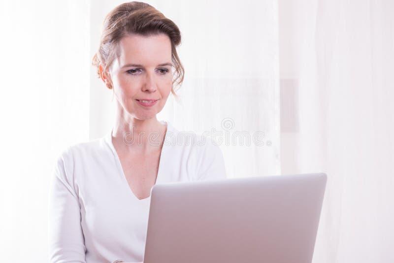 可爱的妇女妇女与在她的手上的计算机一起使用 免版税库存照片