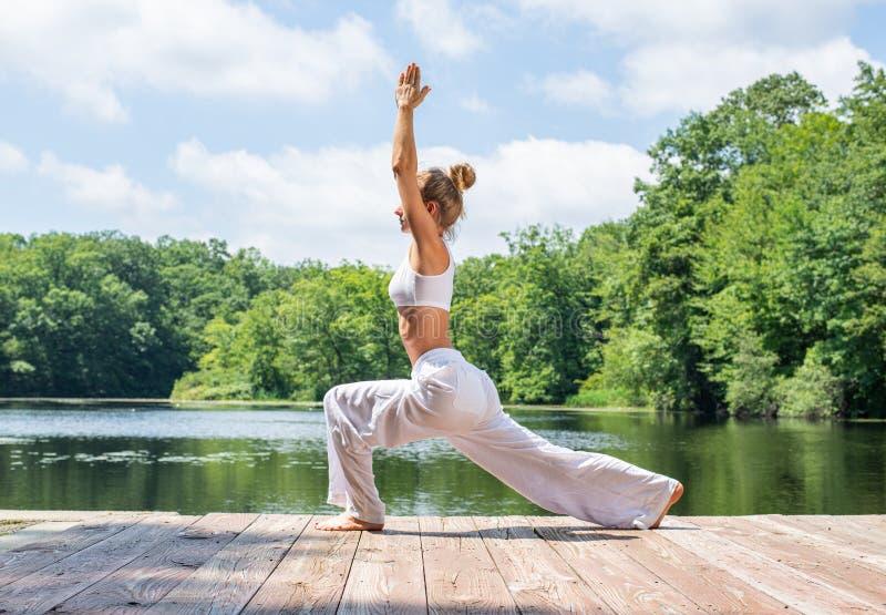 可爱的妇女实践瑜伽,做Virabhadrasana I姿势,站立在战士姿势在湖附近 图库摄影