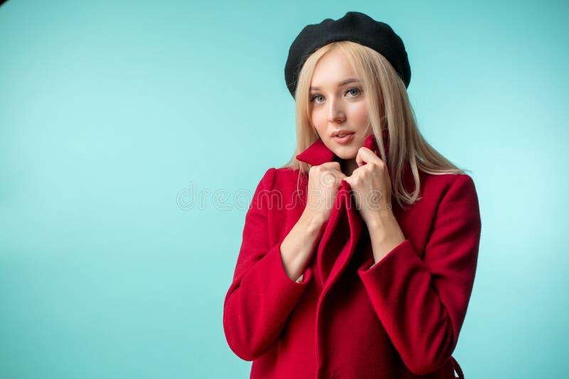 可爱的妇女拿着她新的昂贵的红色外套衣领  库存照片