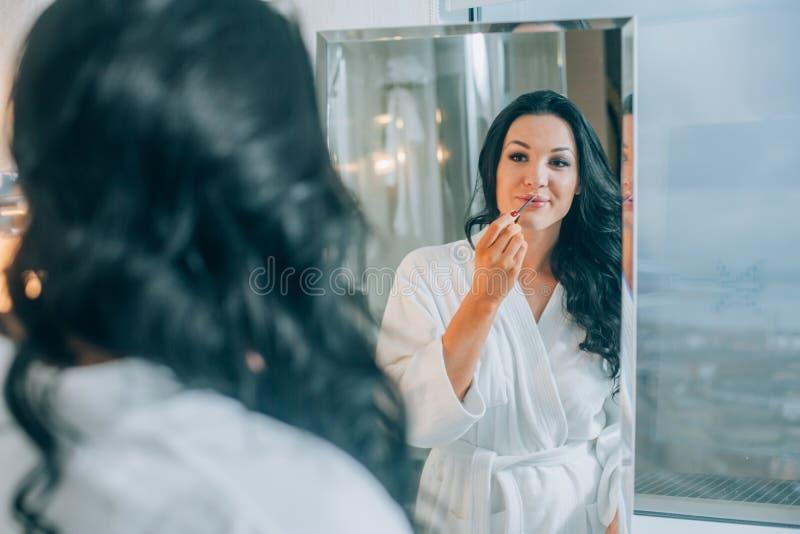 可爱的妇女掠过的牙画象在卫生间里一件白色外套 健康牙 图库摄影