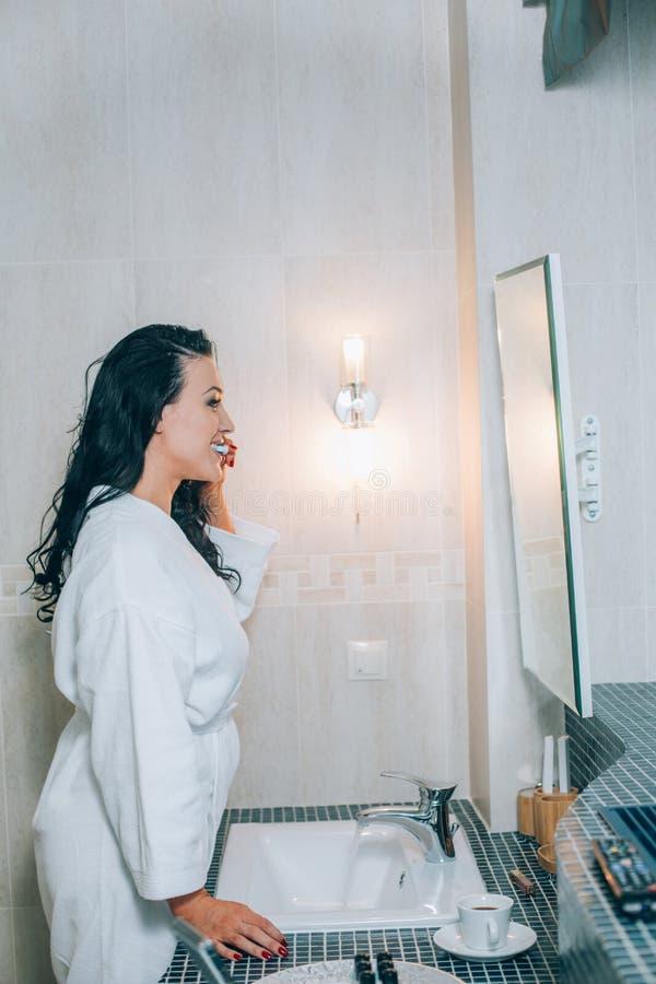 可爱的妇女掠过的牙画象在卫生间里一件白色外套 健康牙 免版税库存图片