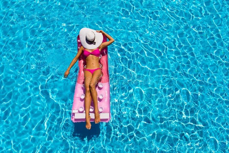 可爱的妇女是松弛在水池的一个浮动床垫 免版税库存图片