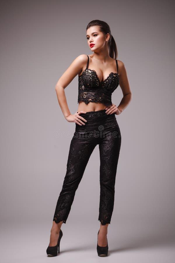 可爱的妇女演播室射击性感的黑上面和长裤的 免版税库存照片