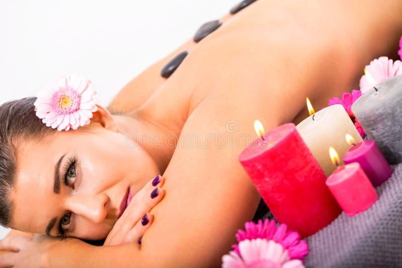 年轻可爱的妇女热的石按摩健康 图库摄影