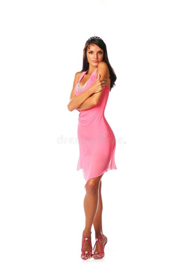 可爱的妇女的明亮的图片典雅的桃红色礼服的有她的盘的腿的 免版税库存图片