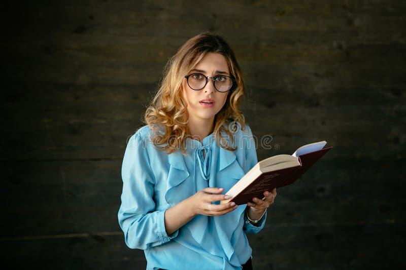 可爱的妇女看起来生气,当读书时 免版税库存照片