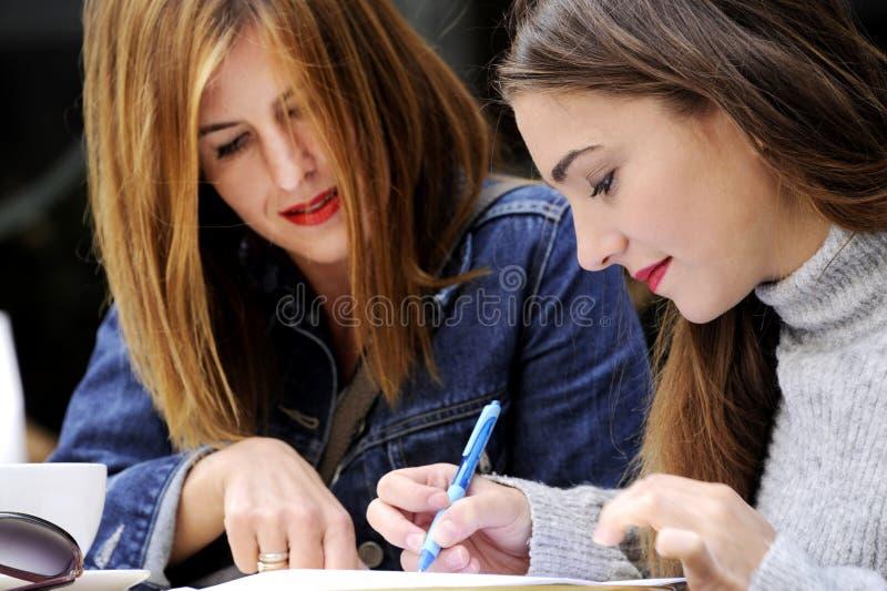 可爱的妇女签署在一个室外咖啡馆的一个协议 免版税库存照片