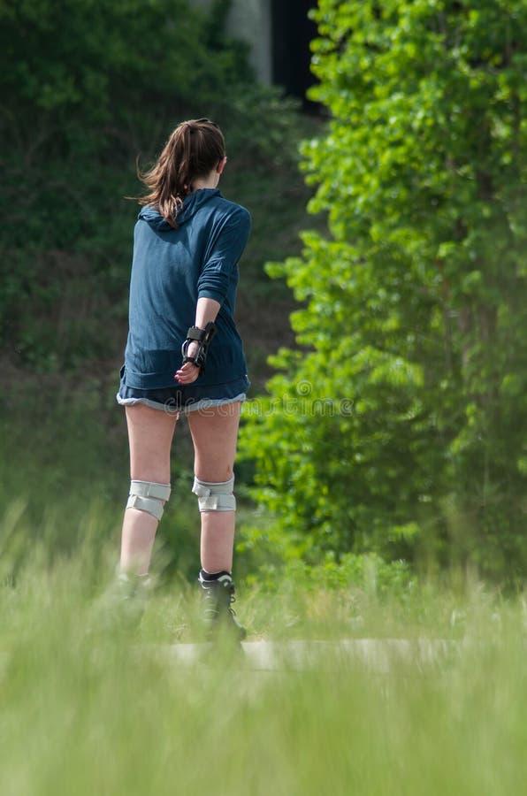 可爱的妇女简而言之驱动胶辊在边界森林里滑冰 图库摄影