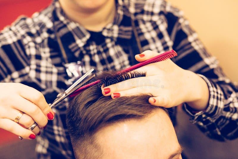年轻可爱的妇女美发师做人的发型 库存照片. 图片 有