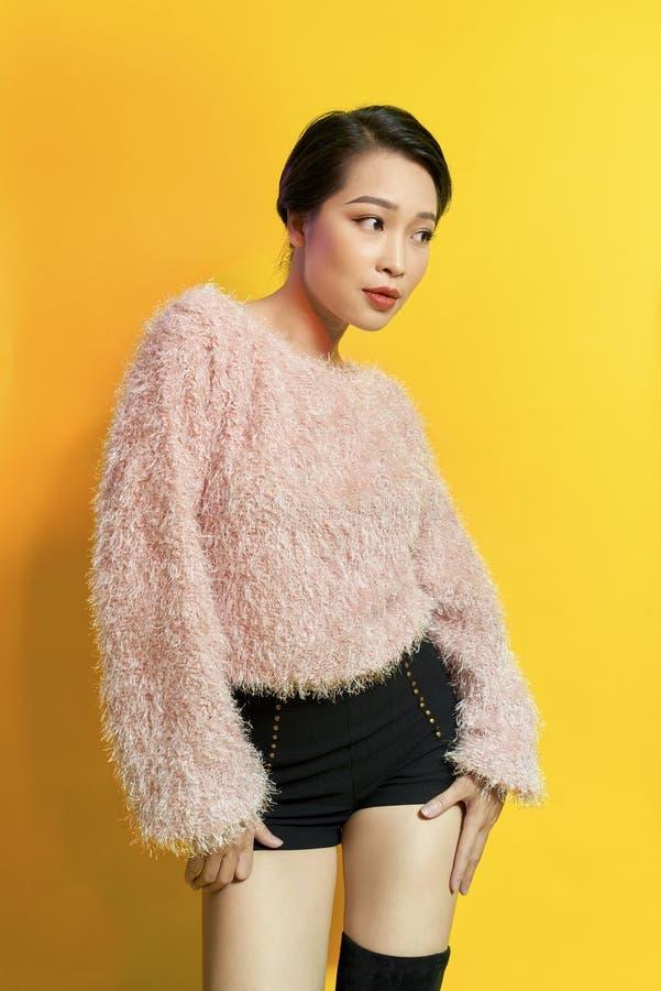 可爱的妇女表现出真实的正面情感在photoshoot期间用桃红色毛皮大衣 活跃迷人的女孩室内画象  免版税库存图片