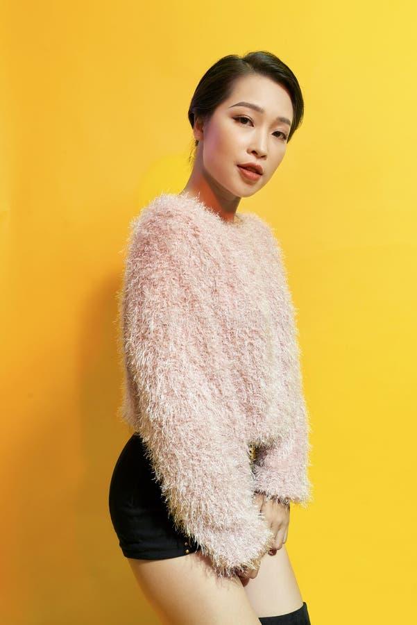 可爱的妇女表现出真实的正面情感在photoshoot期间用桃红色毛皮大衣 活跃迷人的女孩室内画象  图库摄影