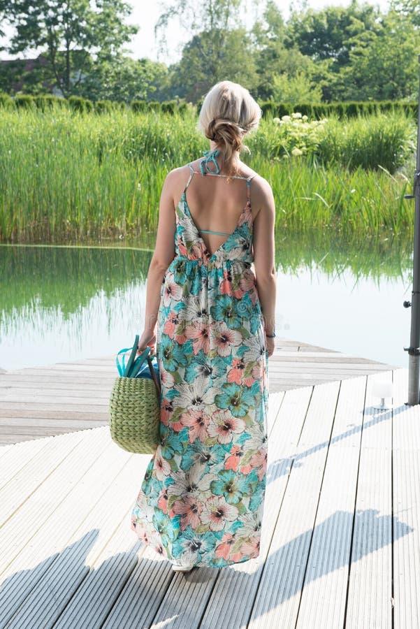 年轻可爱的妇女走到水池 免版税库存照片