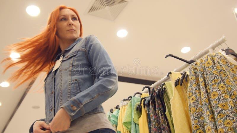 年轻可爱的妇女选择在妇女` s服装店的一件牛仔裤夹克 图库摄影