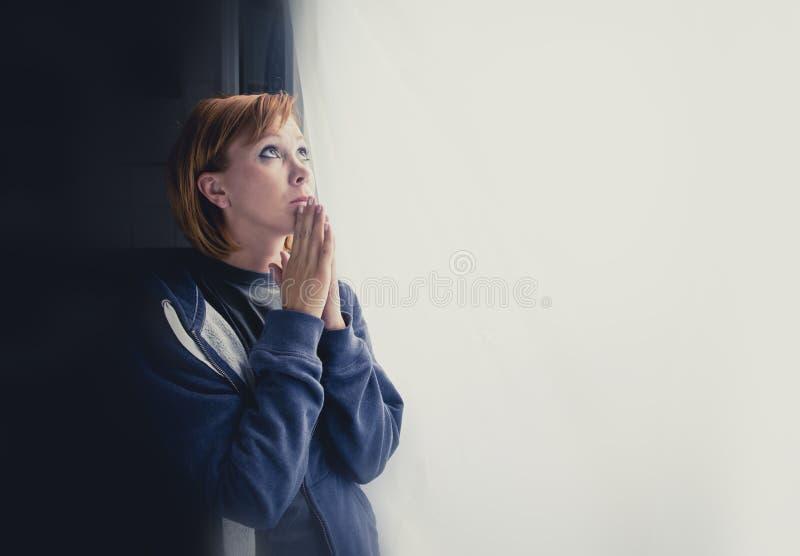 可爱的妇女遭受的消沉说祷告对帮助的神 免版税库存照片