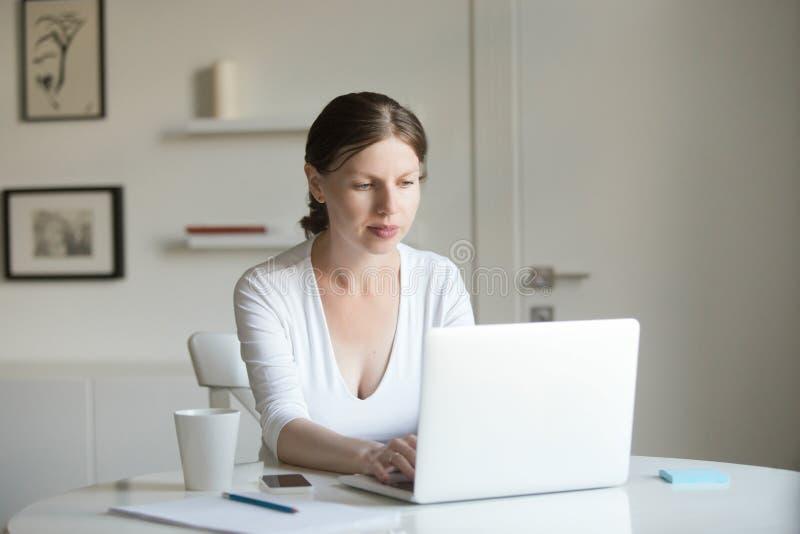 年轻可爱的妇女画象书桌的有膝上型计算机的 免版税库存图片