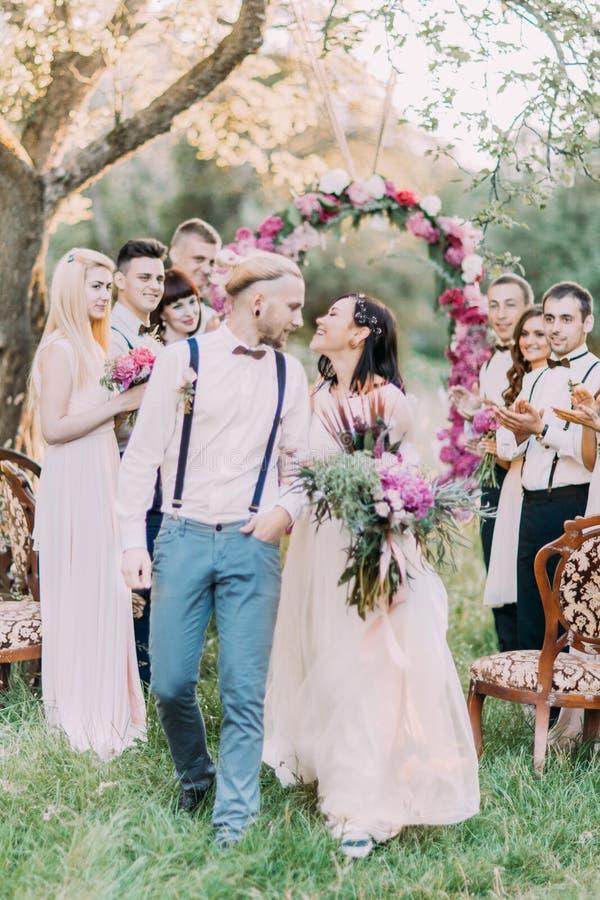 可爱的婚礼的特写镜头照片在晴朗的木头的 在背景的微笑的新婚佳偶夫妇  免版税库存照片