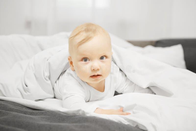可爱的婴孩在床上在温暖的毯子下 免版税库存图片