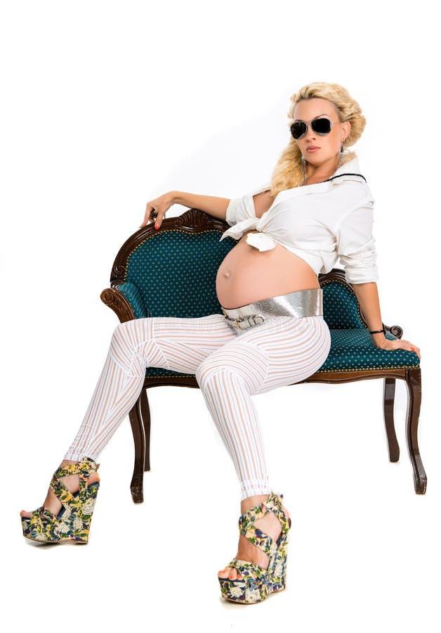 年轻可爱的孕妇坐沙发 免版税库存照片
