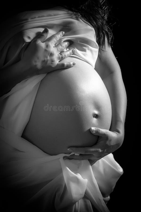 年轻可爱的孕妇的腹部 免版税库存图片