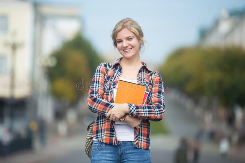 年轻可爱的学生女孩画象反对被弄脏的城市街道的 库存照片