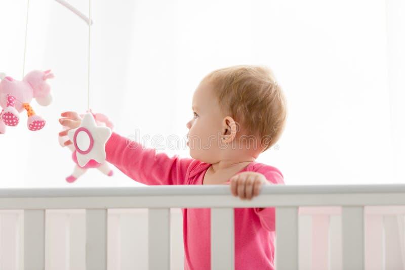可爱的孩子侧视图在桃红色衬衣身分的在小儿床和 免版税库存照片