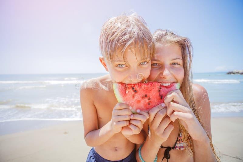 可爱的孩子用在海滩的西瓜 库存图片