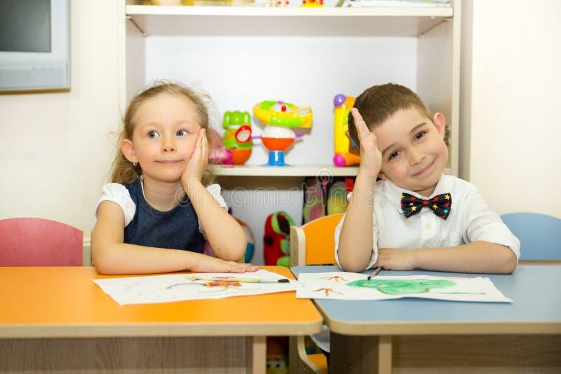 可爱的孩子男孩和女孩在托儿所屋子里画一把刷子和油漆 孩子在幼儿园在蒙台梭利幼儿园类 免版税库存图片
