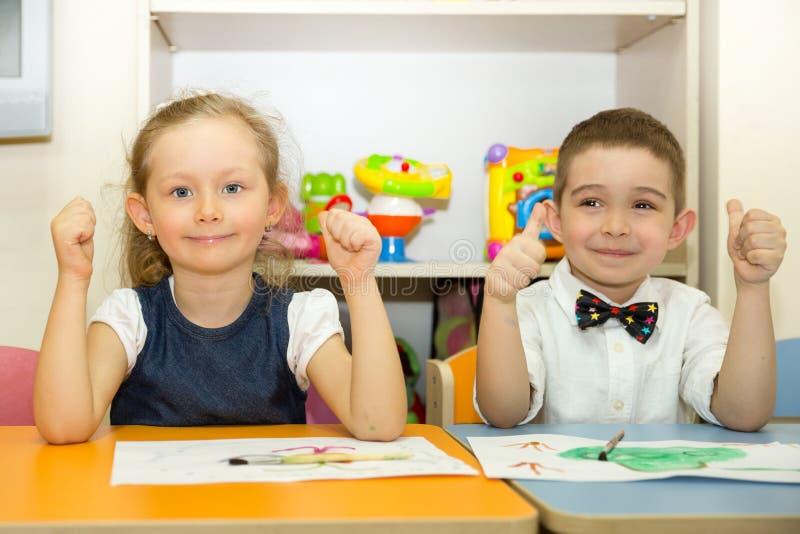 可爱的孩子男孩和女孩在托儿所屋子里画一把刷子和油漆 孩子在幼儿园在蒙台梭利幼儿园类 库存图片