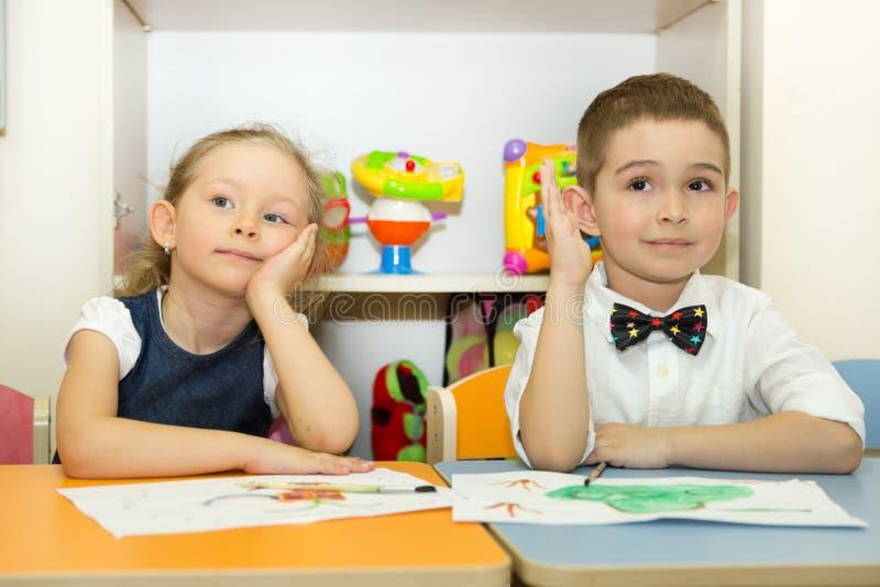可爱的孩子男孩和女孩在托儿所屋子里画一把刷子和油漆 孩子在幼儿园在蒙台梭利幼儿园类 免版税库存照片