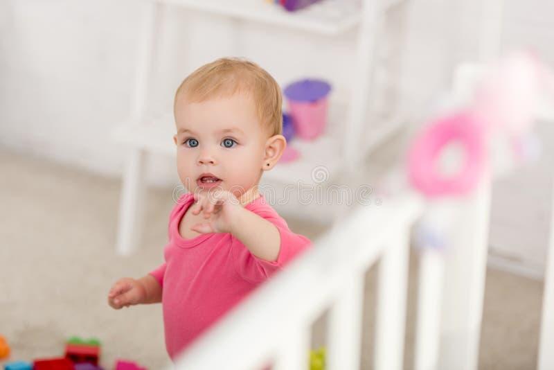 可爱的孩子选择聚焦在桃红色衬衣身分的在小儿床附近 免版税库存照片